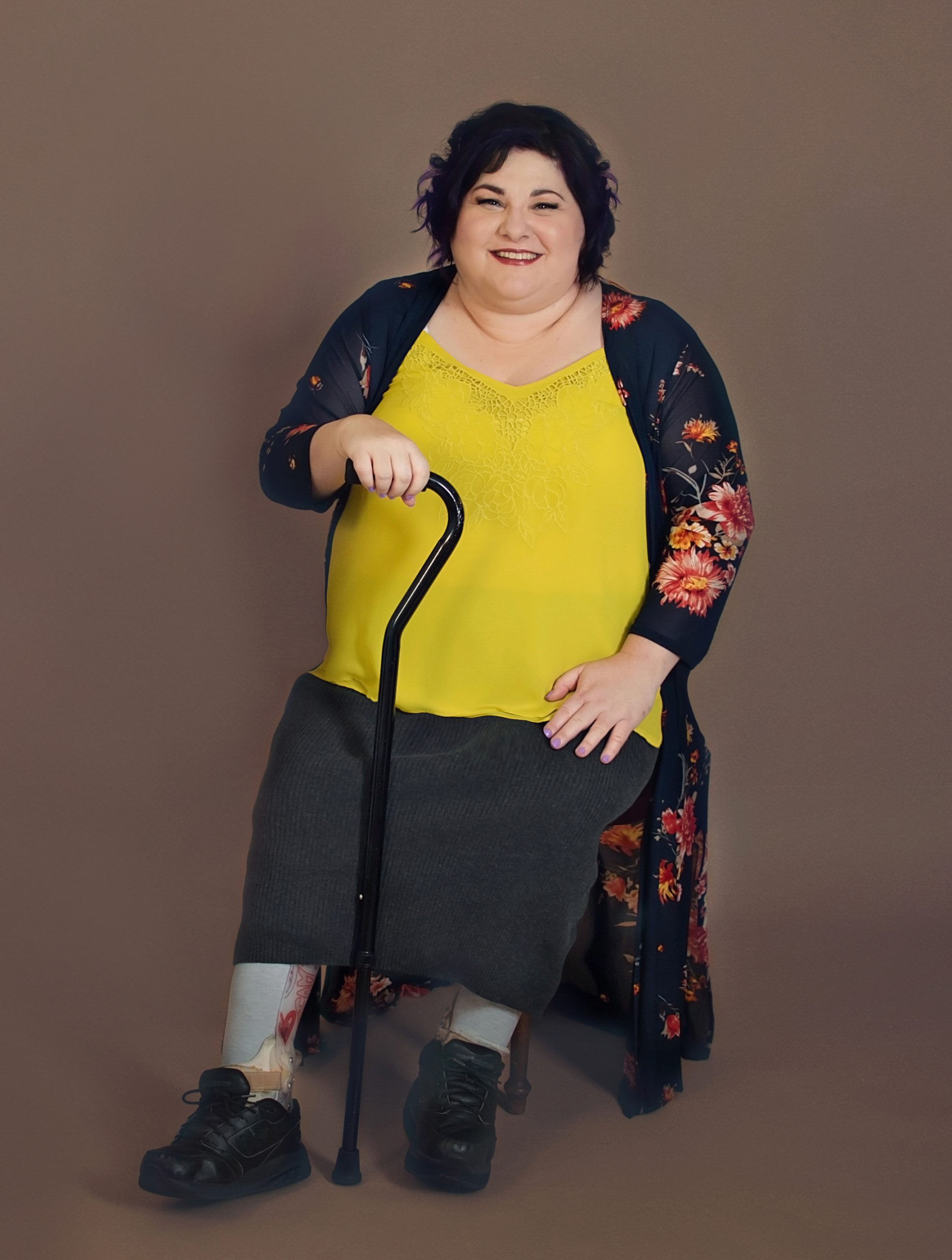 Picture of Donna Herrington sitting and holding her cane