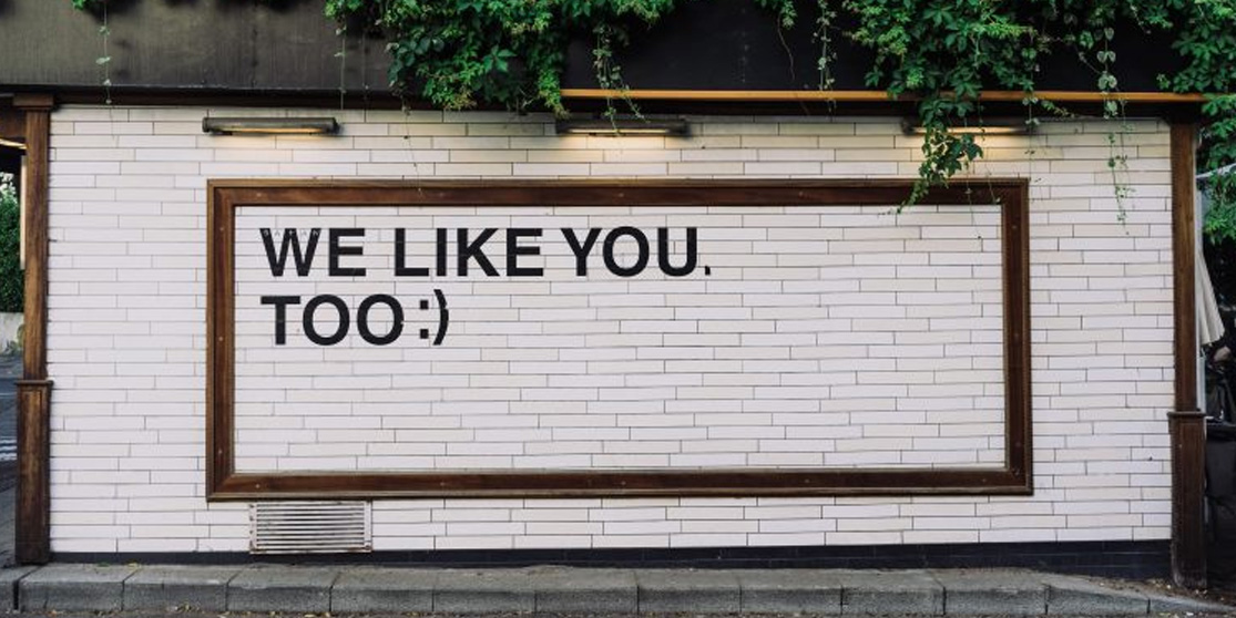 a sign on a building that says we like you too
