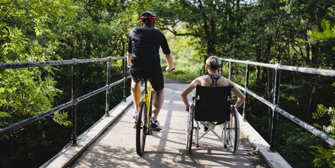 2 people on a trail, one uses a wheelchair, the other is on a bike