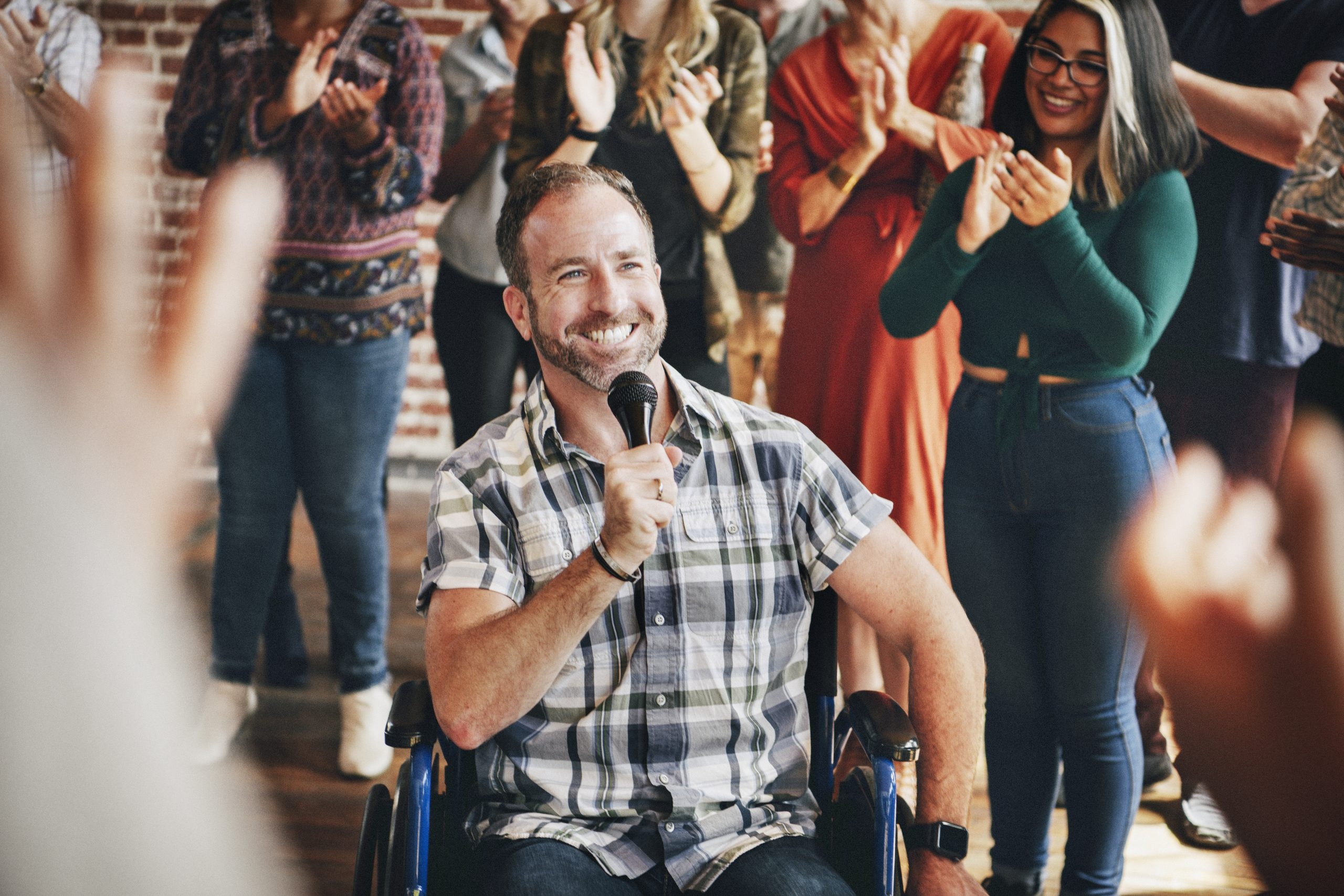 Man in a wheelchair speaking on a microphone in a workshop