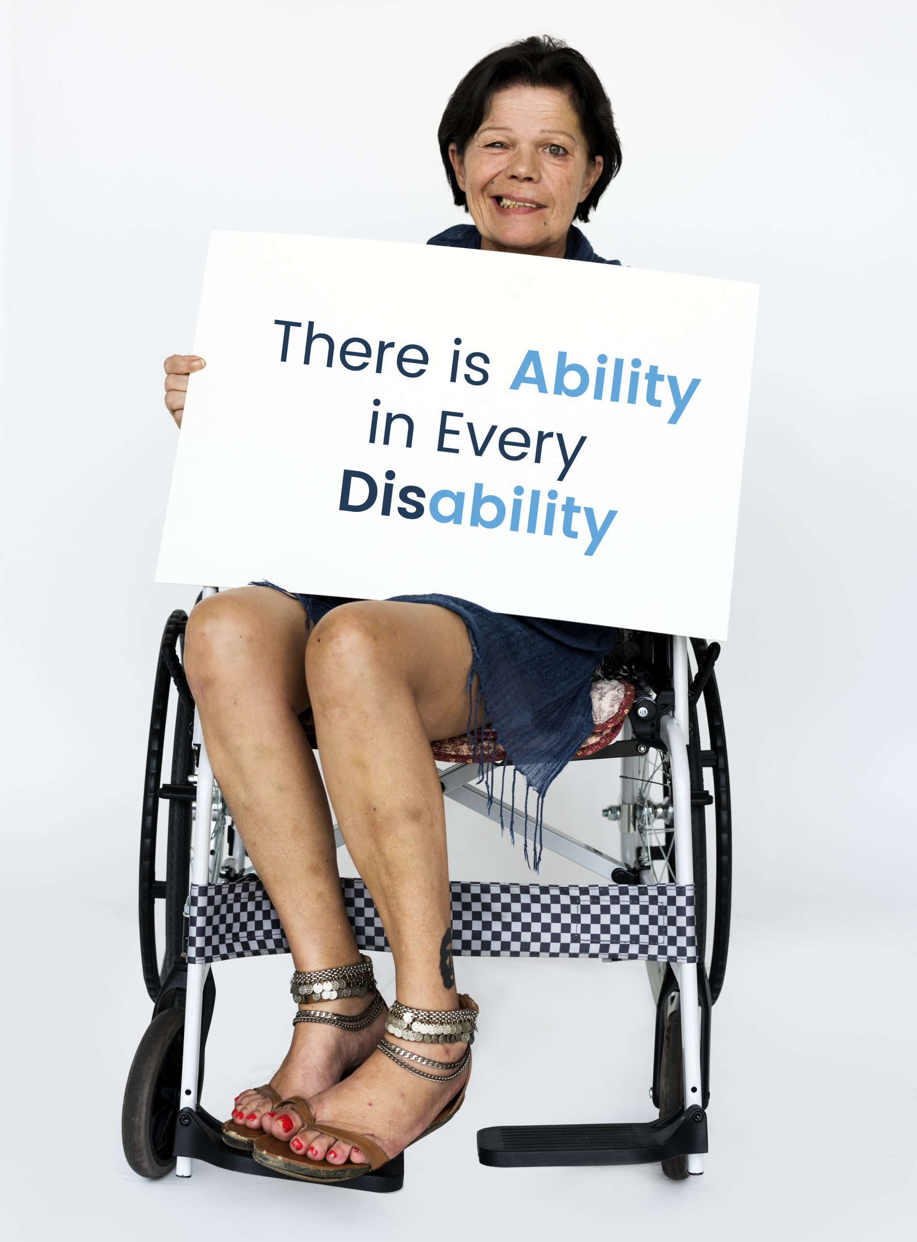 """A woman in a wheelchair holding a sign which says """"There is Ability in every Disability"""""""