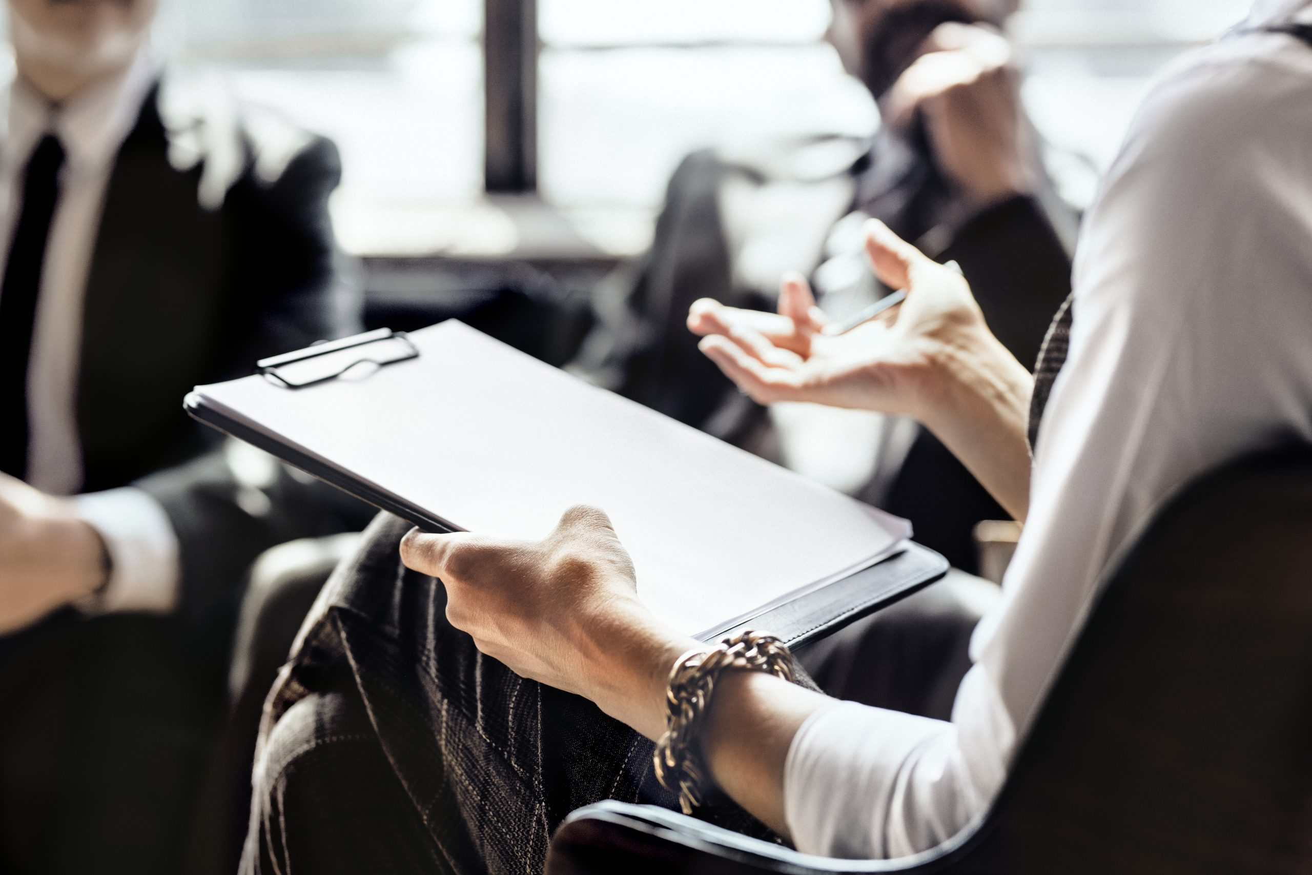 People in a meeting sitting at table, close up of clipboard