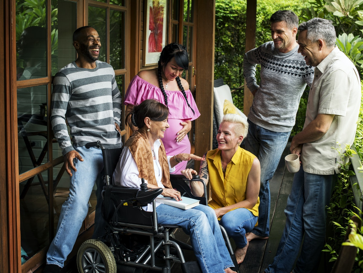 group of people standing, one person uses a wheelchair