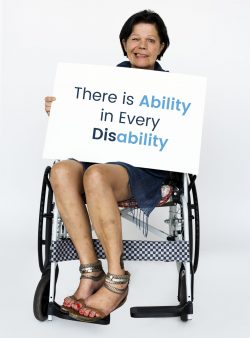 A woman in a wheelchair holding a sign which says